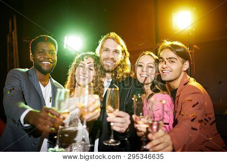 Group Of Jovial Young Multi-ethnic Friends In Stylish Outfits Standing With Flutes In Row Under Fall