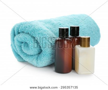 Mini Bottles With Cosmetic Products And Towel On White Background. Hotel Amenities