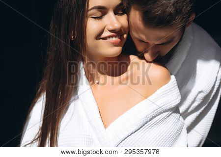 Young Man Gently Kissing Beautiful Woman On Shoulder