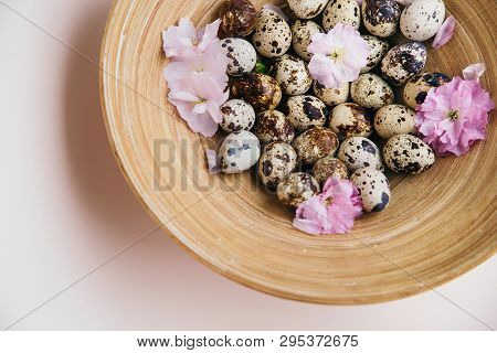 Quail Eggs And Pink Flowers In Wooden Plate Composition On Beige Background. Easter Concept.