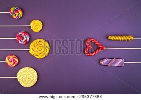 Many Colorful Lollipop Candys Arranged In Two Group And Empty Space  In The Center On Pink Backgroun