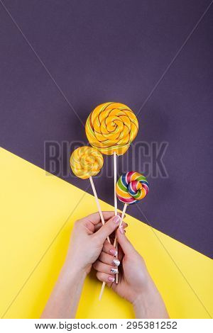 Concept Of Stylish French Manicure, Female Hand Holds Three  Coloroful Yellow Spiraled Round Lollypo