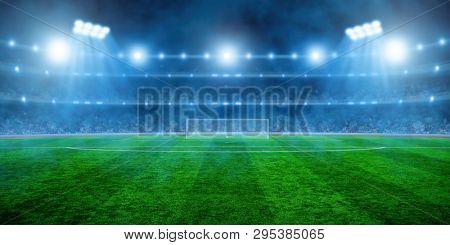 Soccer stadium with illumination, green grass and night  blurred sky