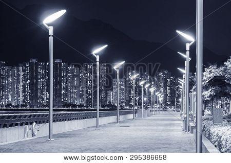 Seaside Promenade And Skyline Of Harbor In Hong Kong City At Night