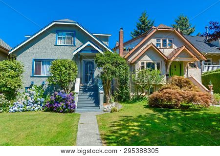 Snug Warm Family Houses Side By Side. Residential House With The Pathway Over Front Yard Lawn On Blu