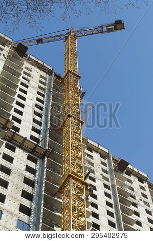 Crane Works In Building Construction Against Blue Sky. Construction Working. Vertical Image