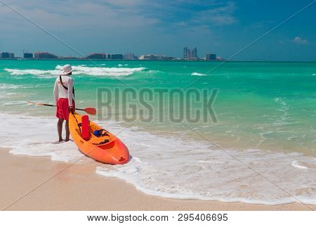 Lifeguard On Duty Seen From Behind With Orange Boat And Paddle In Hand.