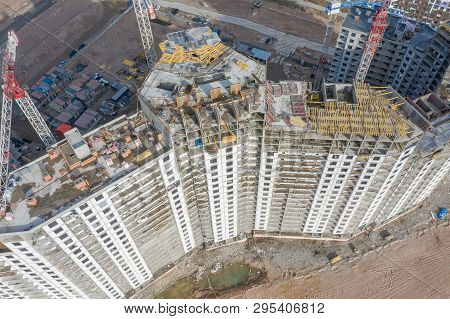 Aerial Top View Of High-rise Residential Buildings Under Construction And Cranes