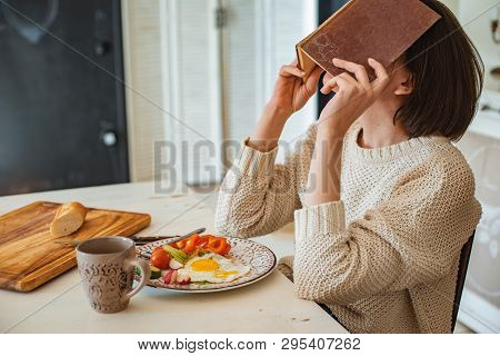 Young Girl Is Reading An Old Book At Breakfast. Close-up Hands And Dinner Table Setting. Country Sty