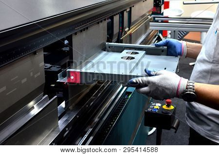Working Operator At A Manufacturing Plant Bending Sheet Metal On A Sheet Hydraulic Bending Machine
