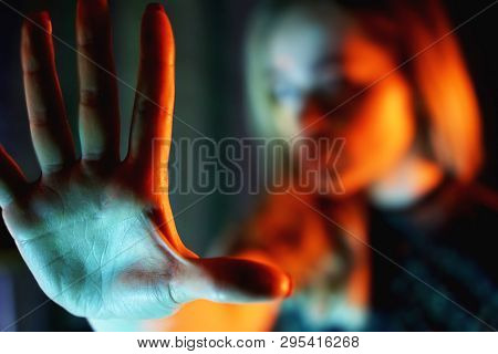 Young woman showing her denial with NO on her hand - neon lights - blurred background poster
