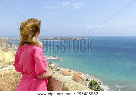 Young Woman With Her Hair In Summer Pink Dress Standing By Blue Sea And Looking Into The Distance