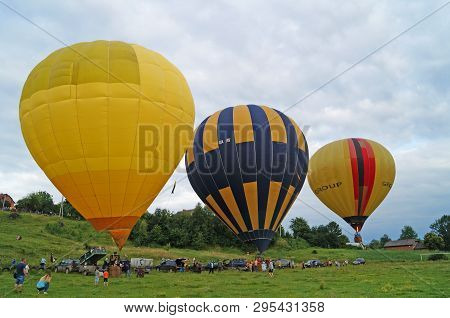 Balloons Of Yellow, Blue, White Are Inflated Before Flying On A Green Glade On A Summer Day.