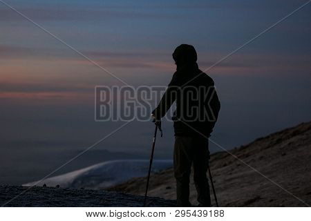 Man In The Black Sportswear Standing On The Top Of The Kilimanjaro In Africa. Enjoys The Beautiful V