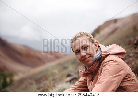 A Blonde Girl In A Beige Windbreaker Sits On The Rocks Among The Red Mountains