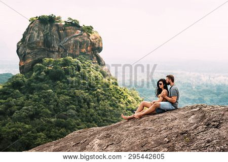 A Couple In Love On A Rock Admires The Beautiful Views. Boy And Girl On The Rock. A Couple In Love T
