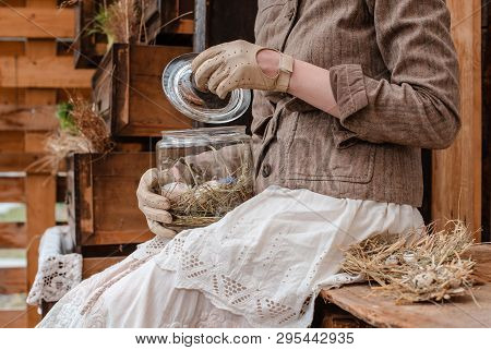 Decorative Easter Eggs In A Glass Jar Close-up On Her Knees And In The Hands Of A Girl In Vintage Cl