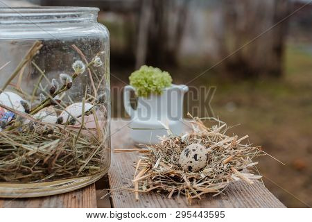 Decorative Easter Eggs On A Served Festive Table In The Garden Outdoors. Farm. Rustic Style.