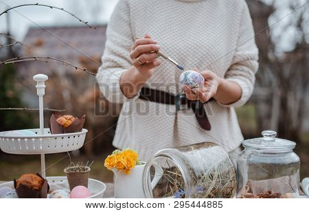 Close-up Of The Girls Hand Paints An Easter Egg In The Garden At The Laid Holiday Table Outdoors. Fa