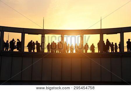 People on the observation deck of Umeda Sky Building, Osaka, Japan. Silhouettes on sunset sky background