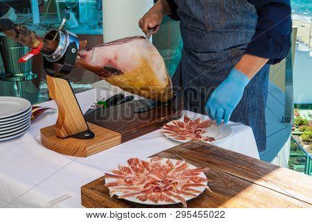Man Preparing And Cutting Iberian Red Ham