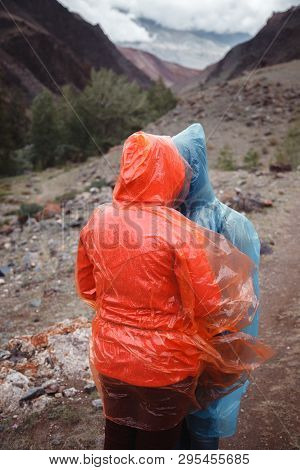 Two Girls With Excellent Mood In Raincoats Travel. Rainy Weather In The Mountains Prevents Trekking