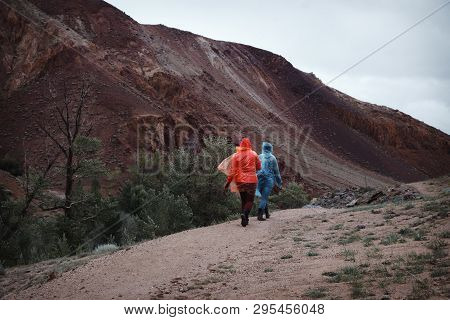 Two Girls With Excellent Mood In Raincoats Travel. Rainy Weather In The Mountains Prevents Trekking.