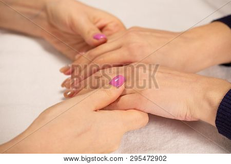 Closeup View Of Hands With Manicure Of Young Woman Nail Treatment By A Specialist In The Salon