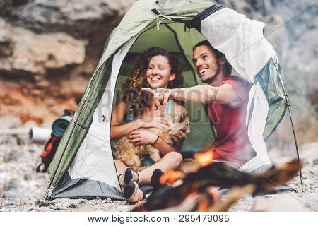 Couple Of Trekker Sitting In The Tent With Their Pet - Happy Man And Woman Having Fun In Vacation Ca