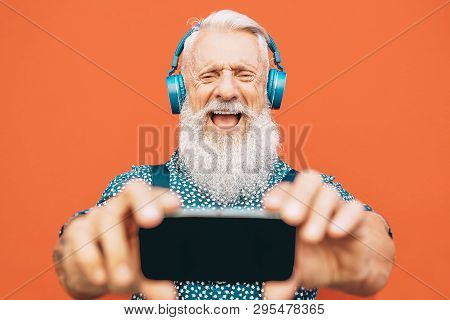 Senior Bearded Man Making Selfie With Mobile Phone While Listening To His Favorite Playlist With Hea