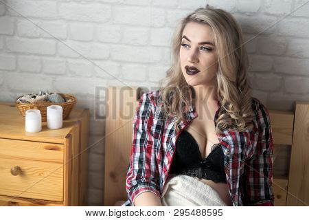 beautiful young blond woman in the bedroom on the bed in lingerie and shirt