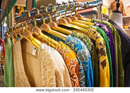 Choice Of Fashion Clothes Of Different Colors On Wooden Hangers