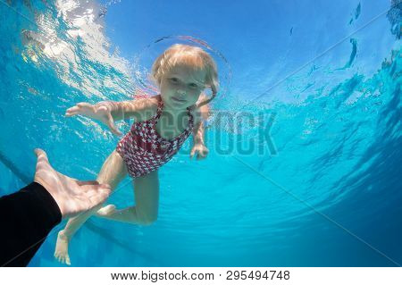 Happy Family In Swimming Pool. Child Jump Deep Down In Pool With Fun - Dive Underwater To Reach Exte