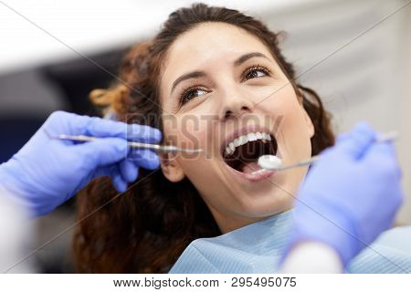 Head And Shoulders Portrait Of Beautiful Young Woman Lying In Dental Chair With Mouth Open During Co