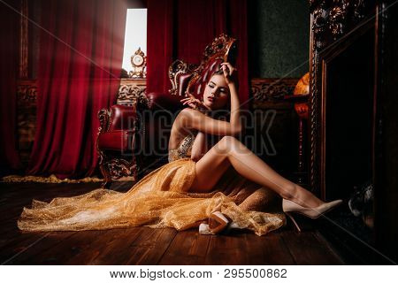 A full length portrait of a mysterious lady in a fluffy long dress posing in the interior. Interior, fashion.