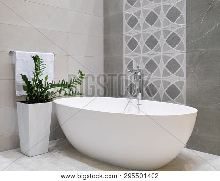 Modern Bathroom Interior Design With White Stone Bathtub, Grey Tiles Wall, Ceramic Flowerpot With Gr