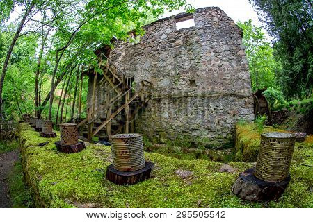 Old Water Mill And Rusted Barrels In The Beautiful Forest Park In Latvia. Moss Covered Ancient Mill