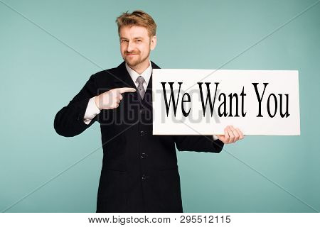 Happy Smiling Young Business Man Points Finger Signboard With Sign We Want You, On Blue Background