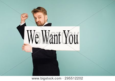Funny Young Business Man Showing Signboard With Sign We Want You, On Blue Background