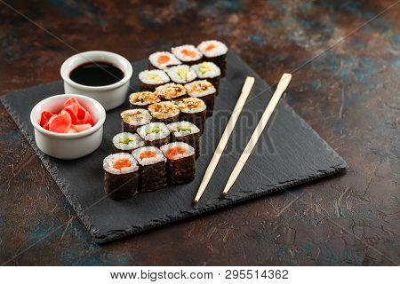Japanese Sushi Rolls Served On Stone Slate On Dark Background. Sushi Rolls, Maki, Pickled Ginger And