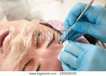 Young Woman In Beauty Salon Does Manual Face Cleaning.
