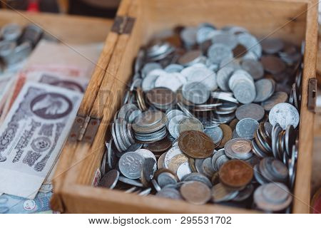 Old Coins Of Different Denominations Are In A Small Wooden Box