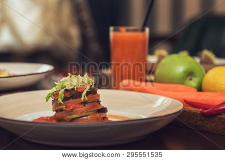 Healthy vegeterian food on brown wood board. Baked vegetables in layers, fruits and carrot juice