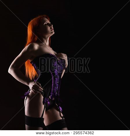 Redhead Sexy Cabaret Dancer In Lingerie And Corset On A Dark Background, Free Space For Your Text