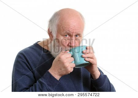 Elderly grey haired man drikns tea or coffee from blue cup isolated on white