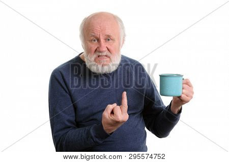 senior grey haired man with blue cup of tea or coffee shows middle finger isolated on white