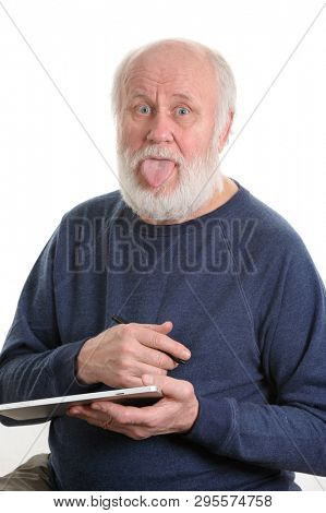 Funny bald and bearded senior man with tongue sticking out using tablet computer, isolated on white