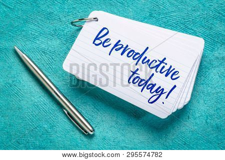 be productive today  reminder - handwriting on a stack of index cards with a cup of coffee and a pen against textured bark paper