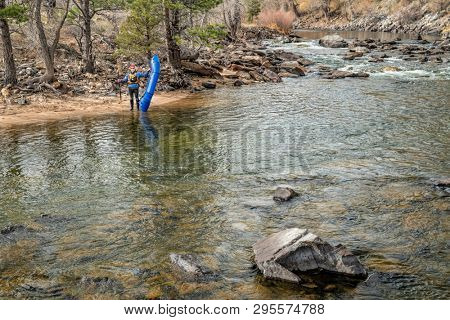 senior paddler with an inflatable packraft on a shore of mountain river in early spring - Poudre River above Fort Collins, Colorado