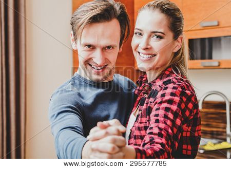 Front view of young married couple dancing in home. Together leisure.